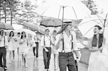 bridal party with umbrellas in the rain